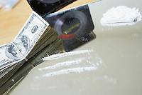 Rows of cocaine on mirror and bundle of money