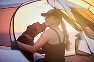 A smiling woman is kissed by her pet boxer dog while sitting inside a camp tent on the beach at sunset.