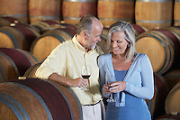 Man and woman with wine-glass aside wine casks