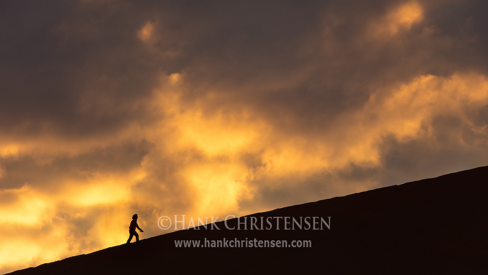 Clouds roil at sunrise behind a lone hiker climing Dune 49, Namib-Naukluft National Park, Namibia.