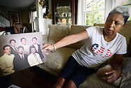 Miriam Rodriguez, of Bethlehem, Pennsylvania holds family photograph  which includes her brother (top right) in her living room  Tuesday, September 26, 2017 in Bethlehem, Pennsylvania. Frank Rodriguez -- who was in state prison for violating parole (smoking marijuana) on a felony (theft of a $1 lemonade) -- was on death vigil in prison for 10 weeks before finally being granted compassionate release. He died a day and a half later. (WILLIAM THOMAS CAIN / For The Philadelphia Inquirer)