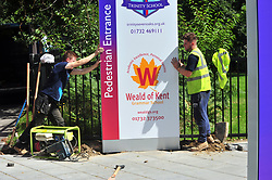 © Licensed to London News Pictures.01/08/2017.<br /> SEVENOAKS,UK.<br /> Workmen erect new sign for new grammar.<br /> New grammar school gets finishing touch before it opens for the new school year in September. The Weald of Kent Grammar school for girls on Seal Hollow Road,Sevenoaks,Kent, shares the site with Trinity School and cost £11 million to build it includes 25 classrooms,dining hall, lecture theatre and sports hall. <br /> Photo credit: Grant Falvey/LNP