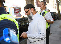 © Licensed to London News Pictures. 19/10/2018. London, UK. Radical preacher ANJEM CHOUDARY is seen using a mobile phone before posing for media outside a bail hostel after being released form Belmarsh Prison in south-east London. Choudary was jailed in 2016 for inviting support for for Islamic State of Iraq and the Levant (ISIS). Photo credit: Ben Cawthra/LNP
