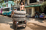 02 MARCH 2014 - MYAWADDY, KAYIN, MYANMAR (BURMA):  A tire seller drives his pedicab loaded with commercial truck tires in Myawaddy, Myanmar. Myawaddy is separated from the Thai border town of Mae Sot by the Moei River. Myawaddy is the most important trading point between Myanmar (Burma) and Thailand.   PHOTO BY JACK KURTZ