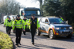 Denham, UK. 6 February, 2020. Police officers arrive to move on environmental activists from Save the Colne Valley, Stop HS2 and Extinction Rebellion walking at a snail's pace along a road in order to block a security vehicle and truck delivering fencing and other supplies to be used for works associated with the HS2 high-speed rail link close to the river Colne at Denham Ford. Works planned in the immediate vicinity include the felling of trees and the construction of a Bailey bridge, compounds and fencing, some of which in a wetland nature reserve forming part of a Site of Metropolitan Importance for Nature Conservation (SMI).
