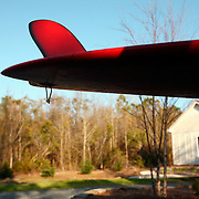 A red surfboard and fin hang out of the back of a pickup truck.
