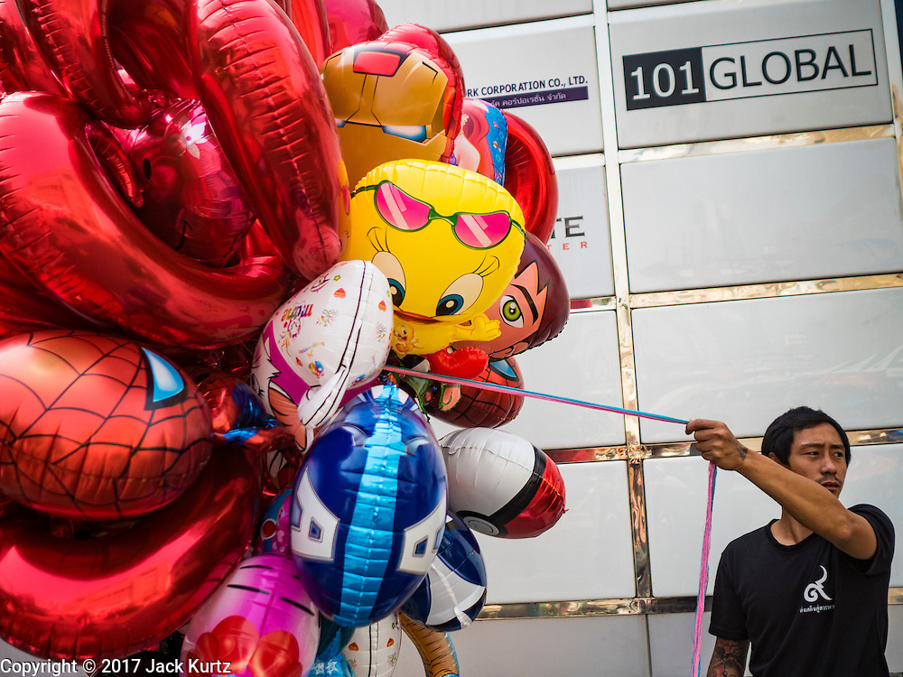 """14 FEBRUARY 2017 - BANGKOK, THAILAND:  A vendor selling inflatable toys waits for customers during a mass wedding in the Bang Rak district in Bangkok. Bang Rak is a popular neighborhood for weddings in Bangkok because it translates as """"Village of Love."""" (Bang translates as village, Rak translates as love.) Hundreds of couples get married in the district on Valentine's Day, which, despite its Catholic origins, is widely celebrated in Thailand.     PHOTO BY JACK KURTZ"""