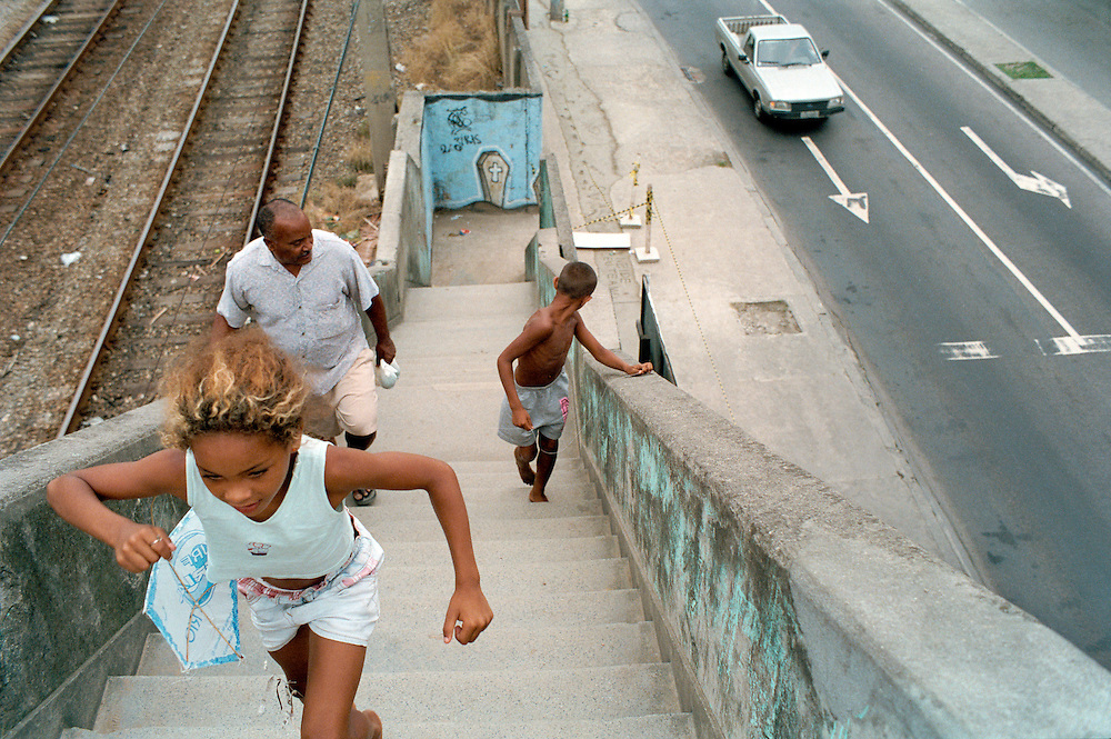 A little girl runs into Vigario Geral. The coffin painted at the bottom of the stairs serves as a reminder of the 21 residents, including 8 children, gunned down by the police in 1993. Rio de Janerio, Brazil. 2001