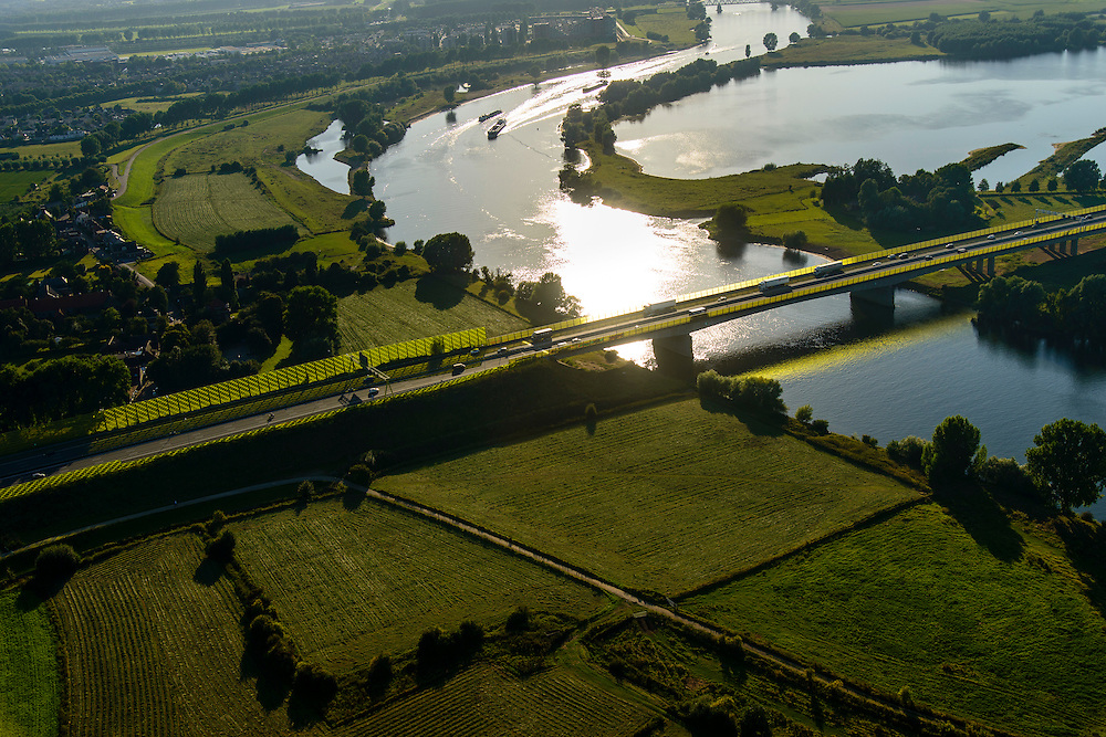 Nederland, Noord-Brabant, Den Bosch, 23-08-2016; brug in Rijksweg A2 over de Maas bij Empel met geluidsscherm in de karakteristiek huiskleur van Rijkswaterstaat. De schaduw op de weg kleurt geel door de lage avondzon. <br /> A2 motorway with bridge A2 over the Meuse at Empel. Yellow colored sound barrier.<br /> luchtfoto (toeslag op standard tarieven);<br /> aerial photo (additional fee required);<br /> copyright foto/photo Siebe Swart