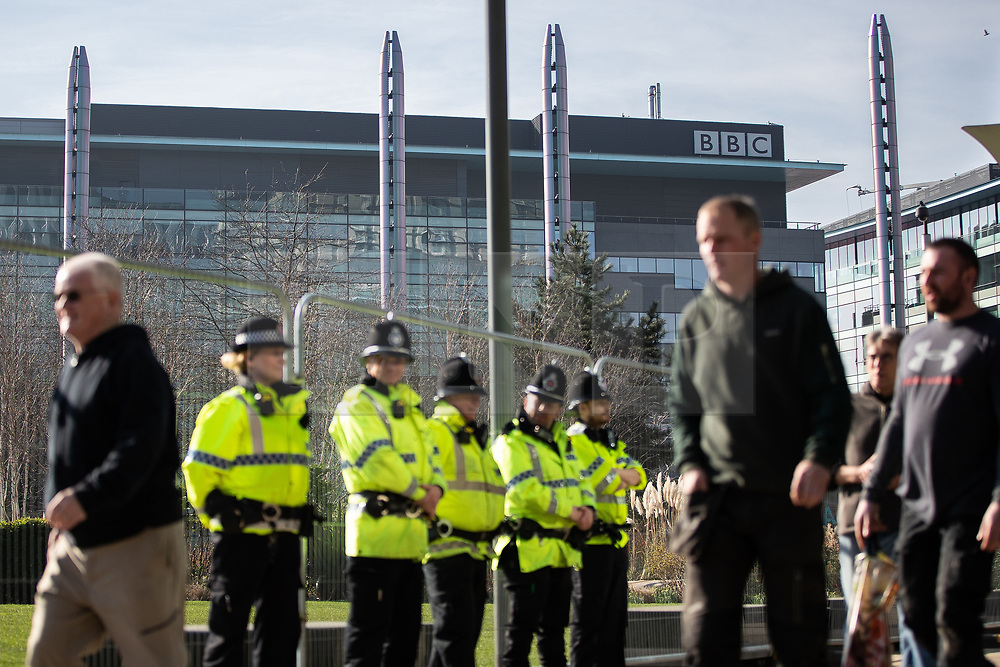 """© Licensed to London News Pictures . 23/02/2019. Salford, UK. Police in front of barriers blocking off access to the BBC at Media City . Supporters of Tommy Robinson (real name Stephen Yaxley-Lennon ) and anti-fascists opposed to the former EDL leader and his followers , gather near to the BBC at Media City to protest , as Yaxley-Lennon hosts a rally showing a home-made documentary , """" Panodrama """" , described as an exposé of the BBC's Panorama documentary series . A BBC Panorama documentary is due to feature an investigation in to Yaxley-Lennon in the near future . Photo credit: Joel Goodman/LNP"""