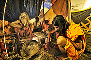 A Naga Sadhu preparing chillum during the Kumbh Mela..The Indian Sadhu's (holy men) have been smoking chillums for thousands of years, and the spiritual meaning of this is comparable to the drinking of red wine by Catholics. At their rituals, the chillum is prepared with a combination of charas (herbs) and tobacco. Through a Hindu ceremony, the Hindu god Shiva was called upon, the Sadhus believing that Shiva would enter into the smoker. In the ceremony, a wet Safi cloth is used, a stone inserted, and the mixture placed into the chillum. The chillum's mouth piece is cupped in two hands and forms a closed prism, as the smoker inhales the smoke without the lips touching the pipe. He puffs violently to light the chillum sufficiently to be passed to the person to the right. In the ceremony of the Jamaican Rastas, the chillum used is made of a cow's horn and wood..