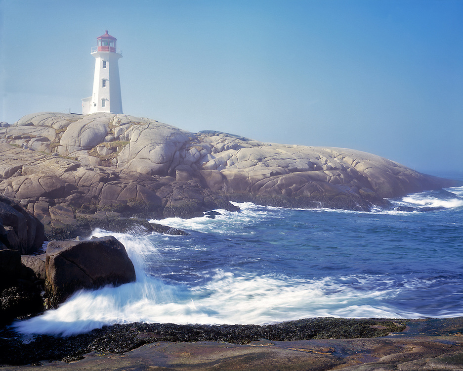 The wind whips the Atlantic Ocean waves into Peggy's Cove Lighthouse in Nova Scotia, Canada.