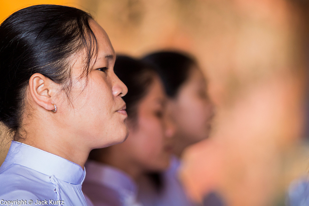 "29 MARCH 2012 - TAY NINH, VIETNAM:  A woman prays during noon services at the Cao Dai Holy See in Tay Ninh, Vietnam. Cao Dai (also Caodaiism) is a syncretistic, monotheistic religion, officially established in the city of Tây Ninh, southern Vietnam in 1926. Cao means ""high"" and ""Dai"" means ""dais"" (as in a platform or altar raised above the surrounding level to give prominence to the person on it). Estimates of Cao Dai adherents in Vietnam vary, but most sources give two to three million, but there may be up to six million. An additional 30,000 Vietnamese exiles, in the United States, Europe, and Australia are Cao Dai followers. During the Vietnam's wars from 1945-1975, members of Cao Dai were active in political and military struggles, both against French colonial forces and Prime Minister Ngo Dinh Diem of South Vietnam. Their opposition to the communist forces until 1975 was a factor in their repression after the fall of Saigon in 1975, when the incoming communist government proscribed the practice of Cao Dai. In 1997, the Cao Dai was granted legal recognition. Cao Dai's pantheon of saints includes such diverse figures as the Buddha, Confucius, Jesus Christ, Muhammad, Pericles, Julius Caesar, Joan of Arc, Victor Hugo, and the Chinese revolutionary leader Sun Yat-sen. These are honored at Cao Dai temples, along with ancestors.     PHOTO BY JACK KURTZ"