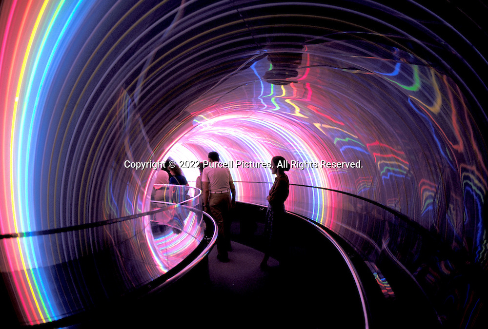Visitors ride a moving platform through a neon tunnel of light at the EPCOT theme park.