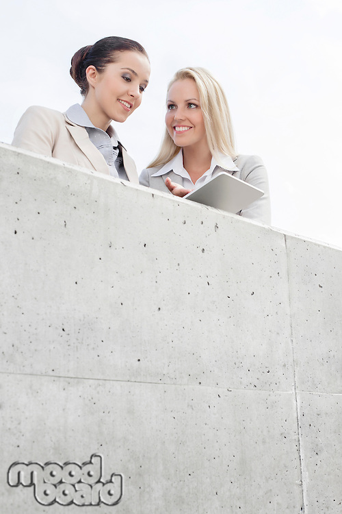 Low angle view of smiling business executives using digital tablet on office terrace against sky