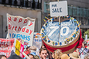 A giant birthday cake for the NHS - #OurNHS70: free, for all, forever a protest and celebration march in honour of the 70 year history of the National Health Service. Organised by: The People's Assembly, Trades Union Congress, Unison, Unite, GMB, British Medical Association, Royal College of Nursing, Royal College of Midwives amongst others.