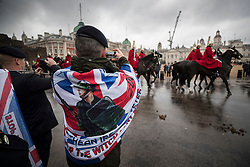 © Licensed to London News Pictures. 03/02/2018. London, UK. A former soldier, wrapped in a flag depicting the troubles in Northern Ireland, photographs members of  Household Cavalry as they make there way across Horse Guards Parade during a Veterans for Justice March in central London .Photo credit: Peter Macdiarmid/LNP