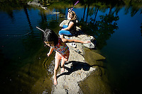 JEROME A. POLLOS/Press..Makayla Pellman, 10, walks along a rocky point at Falls Park as April O'Dell, 15, casts her line into the water Thursday during a fishing derby for children from St. Vincent de Paul's transitional housing. This is the second year the event was organized by St. Luke's Men's Club as way to provide the children with a recreational outlet.