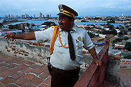 Un hombre vestido de vigilante,  informa de alguna situación. Al fondo se puede ver parte de la bahía, casas y grandes edificios que conforman la ciudad. Cartagena de Indias,  2001 (Ramón Lepage / Orinoquiaphoto)     The fortified wall of Cartagena is in excellent condition and stretches more-or-less unbroken round a good portion of the Old Town. It is a pleasure for locals well as visitors to walk and observe the colonial architecture and excellent view of the Caribbean ocean..
