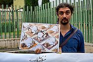 """Roma, 19 Settembre  2014<br /> Manifestazione  contro  ISIS ( Stato Islamico).<br /> Uno striscione con la scritta: """"ISIS non è Islam"""" esposto da un gruppo di italiani ed immigrati davanti alla Moschea Grande  di Roma, durante la preghiera del Venerdi. Manifestante  con i disegni di artisti siriani contro ISIS<br /> Rome, 19 September 2014 <br /> Demonstration against ISIS (Islamic State). <br /> A banner with the inscription: """"ISIS is not Islam"""" exhibited by a group of Italian and immigrants  in front of the Grand Mosque of Rome, during prayers on Friday. Protestor with the designs of Syrian artists against ISIS"""