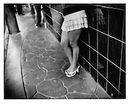 "La Paradita (Woman who stand against the wall). Prostitute in short frilly skirt lines up for selection of passing male customers in the La Coahuila red light district, which is just a couple of hundred meters from the border, Tijuana, Mexico.   Prostitution is legal in Tijuana and limited to three ""zones of tolerance"".  Lack of water is a major factor contributing to pervasive poverty south of the border."