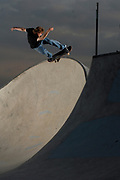 A skateboarder performing in a skate park.