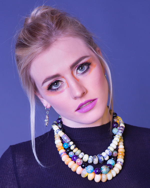 Beauty headshot of Houston model and actress Savannah O'Hara wearing exotic makeup and gemstone beads.