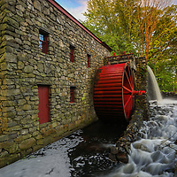 The Sudbury Grist Mill in Central Massachusetts on a beautiful spring morning. This is a more intimate view of this historic watermill. The warm morning light painted the tree canopy in gorgeous spring colors which stand in nice contrast with the historic landmark and red waterwheel. A long exposure setting created the flowing water effect of the brook.<br />