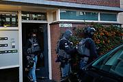 Leden van de Dienst Speciale Interventies, de eenheid die zich onder ander bezighoudt met terreur, verlaat de woning aan de Oudenoord in Utrecht waar de verdachte van de schietpartij in de tram in Utrecht is aangehouden.