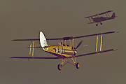 "Two Tigermoths cruise above Hood Aerodrome in Masterton, New Zealand. These flight demonstrations and static displays were part of the 2012 commemoration of ANZAC Day by The Vintage Aviator in Masterton, New Zealand. ANZAC (Australian and New Zealand Army Corps) Day is observed to remember ANZACs who served at Gallipoli during World War 1 and more generally all those who served and died for their countries. The Vintage Aviator Ltd is an aircraft restoration company and manufacturer based in New Zealand. On their website, thevintageaviator.co.nz, The Vintage Aviator list their primary aim as ""to build WW1 aircraft, engines and propellers to the same exacting standards they were originally made over 90 years ago"". The Vintage Aviator now boasts a fleet of WW1 aircraft including those originally made by Albatros, Fokker, Sopwith, Bristol, Nieuport and the Royal Aircraft Factory."