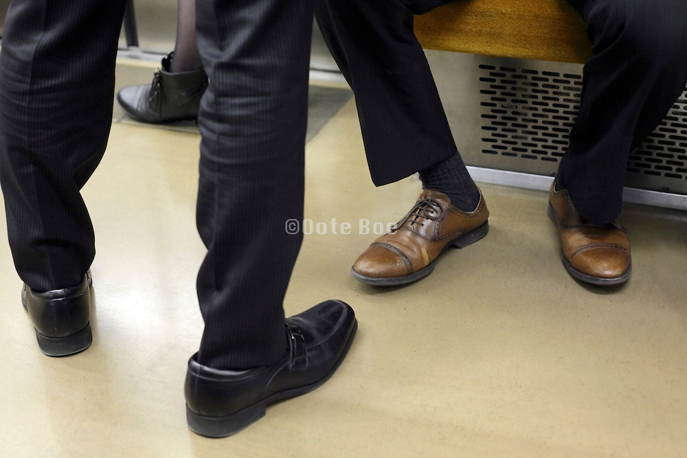 legs and shoes of businessmen during train commute Tokyo Japan