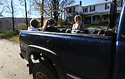 Students from left, Calais Larson, Caroline Benson, and Julia Christensen, headed to an upper field to harvest potatoes, wait in the back of a pickup at the Mountain School
