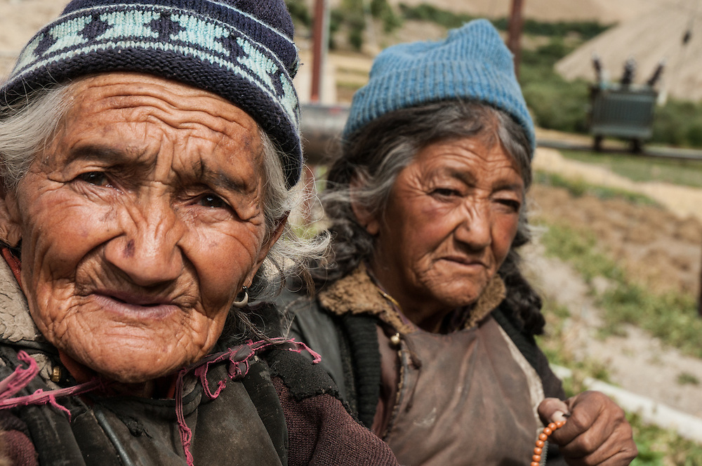 Two old women and a goat skin wrapped around their shoulders in Ladakh, Northern India.
