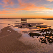 Aerial panoramic dusk and historic life-guard building at Fuseta fishing town, in Ria Formosa wetlands nature conservation park, Algarve. Portugal.