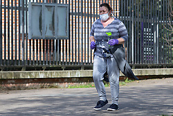 © Licensed to London News Pictures. 04/04/2020. London, UK. A member of the wears a medical mask and latex gloves as she exercises in Greenwich Park . The Government has announced a lockdown to slow the spread of Coronavirus and reduce pressure on the NHS. Photo credit: George Cracknell Wright/LNP