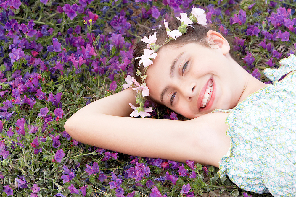 Smiling Pre-teen girl with flower headdress lying arm behind head in field of flowers elevated view