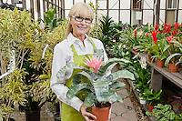 Portrait of a senior gardener holding pot plant in garden center