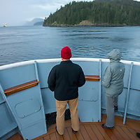 Guests on the bow of the National Geographic Sea Lion watch a large cruise ship approach in the distance on the Georgia Strait on the Inside Passage of British Columbia, Canada.