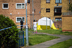 A local resident carrying a baby walks past the tent marking the spot where a 24 year old male known locally as Mali died at the scene of yet another murder, this time on an estate on Crows Road in Barking, London, May 18 2018.