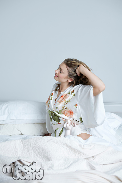 Young woman in dressing gown stretching in bed