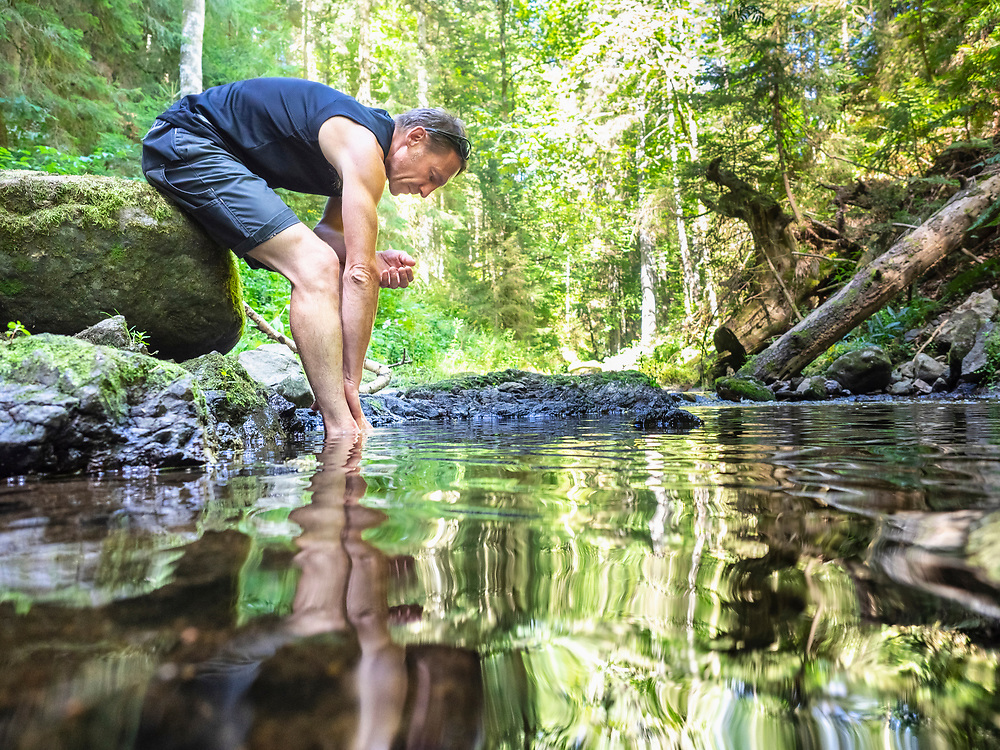 Male hiker taking rest at riverbank, Baden-Wuerttemerg, Germany