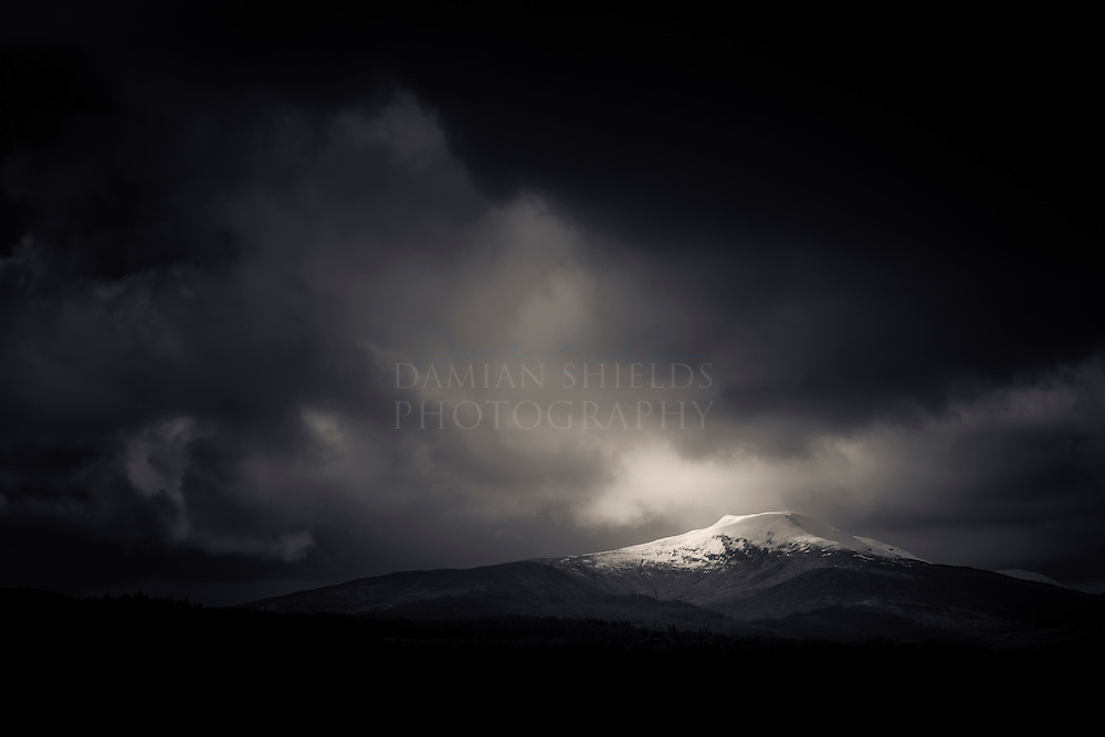 Runner up - Landscape category - Scottish Landscape Photographer of the Year. <br /> <br /> I shot this image during a pit-stop at the Commando Memorial at Spean Bridge. I was admiring the bronzed<br /> soldiers view of the mighty Nevis range to the south, the hills encased in a thick layer of snow. As my<br /> eye turned west I was stuck by the lovely profile of Stob a Ghrianain rising above a thick strip of<br /> pines. The soft and thick cloud formations moving over the scene made for a perfect backdrop to the crisp<br /> lines and contrasts created by the strong sunlight and I accentuated the mood in post processing by<br /> taking the exposure down to draw you in to the spill of light on the peak.