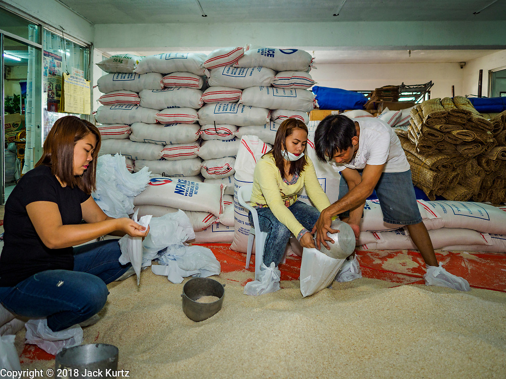 "22 JANUARY 2018 - LEGAZPI, ALBAY, PHILIPPINES:  JANE BLANCA, left, ANN BACEA, and WANY MATEBUENA, employees of the Albay Provincial Social Welfare and Development Office package emergency food supplies to be delivered to the evacuees from the Mayon volcano eruptions. There were a series of eruptions on the Mayon volcano near Legazpi Monday. The eruptions started Sunday night and continued through the day. At about midday the volcano sent a plume of ash and smoke towering over Camalig, the largest municipality near the volcano. The Philippine Institute of Volcanology and Seismology (PHIVOLCS) extended the six kilometer danger zone to eight kilometers and raised the alert level from three to four. This is the first time the alert level has been at four since 2009. A level four alert means a ""Hazardous Eruption is Imminent"" and there is ""intense unrest"" in the volcano. The Mayon volcano is the most active volcano in the Philippines. Sunday and Monday's eruptions caused ash falls in several communities but there were no known injuries.   PHOTO BY JACK KURTZ"