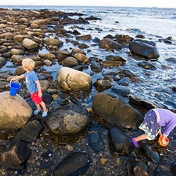 A young brother and sister exploring a tidepool in Odiorne State Park in Rye, New Hampshire.