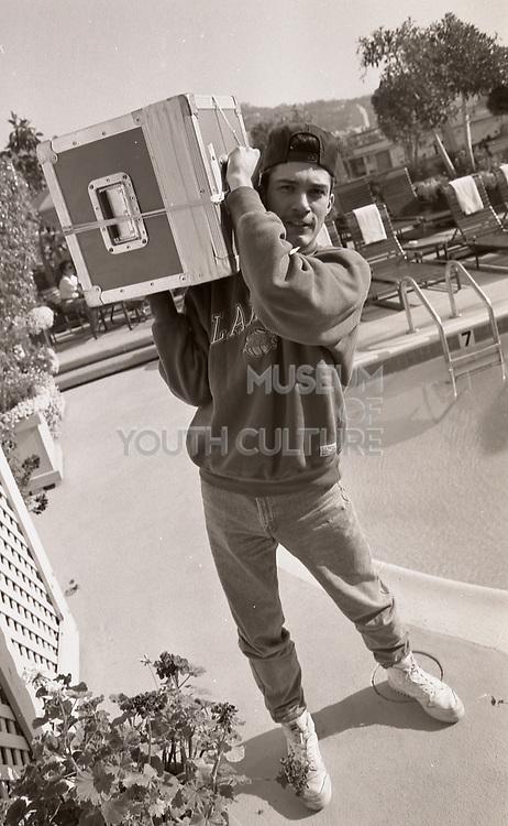 DJ Joey Beltram carrying some gear on the roof of a hotel, LA, 1980s