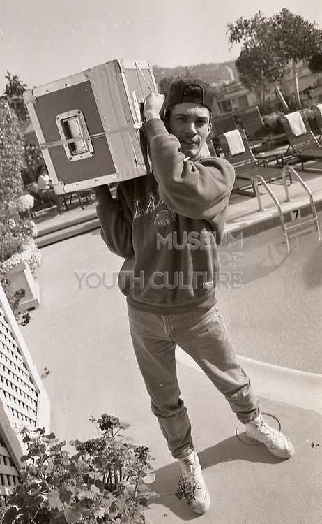 DJ Joey Beltram carrying some gear on the roof of a hotel, LA, 1980s