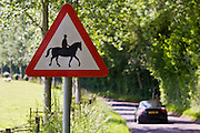 Car passes Accompanied horses or ponies warning sign by roadside, Dorset, UK