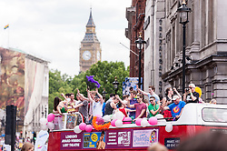 © Licensed to London News Pictures. 27/06/2015. Trafalgar Square, London, UK. An open topped double-decker bus makes its way down Whitehall as participants take part in the annual Pride parade in London, one of the world's largest LGBT+ events.  Hundred of thousands of people gathered to watch the events on a hot summer's afternoon. Photo credit : Stephen Chung/LNP