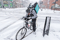 Deliveroo rider checking an address on his mobile phone in a snow storm.