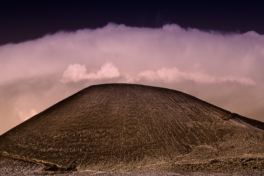 Storm front over extinct volcano cone in the Cinder Cone National Monument on Mojave National Preserve.